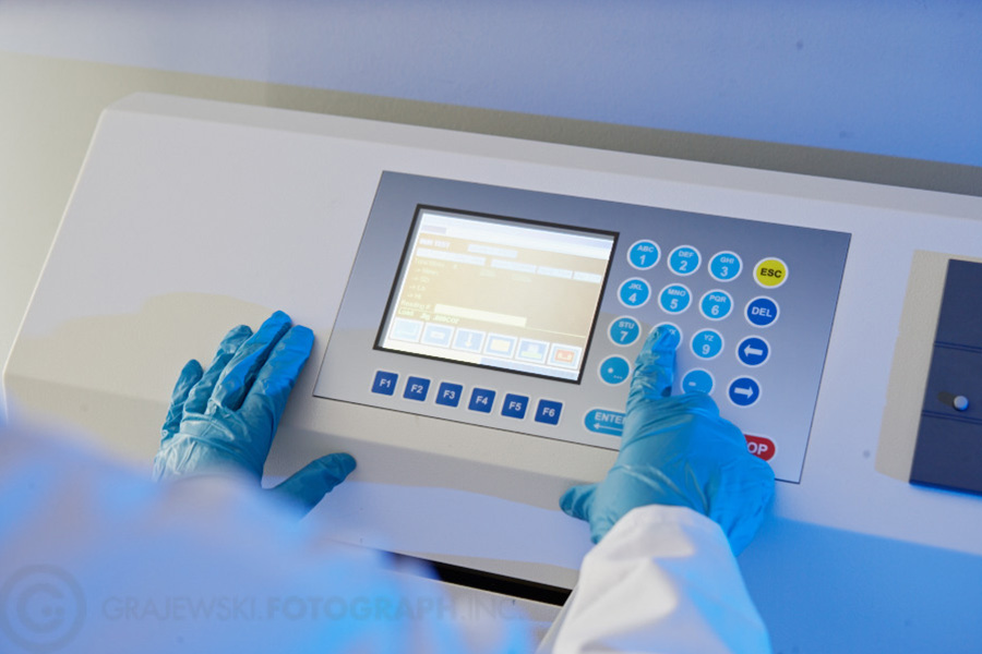 technician calibrating machine wearing blue latex gloves